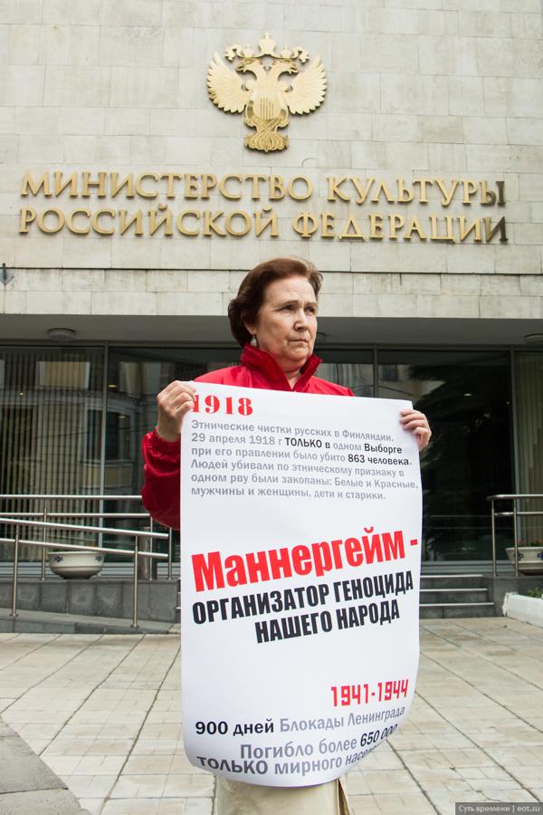Активистка «Сути времени» перед входом в Министерство культуры в Москве с плакатом «Маннергейм — организатор геноцида нашего народа», эстафета пикетов заканчивается