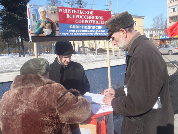 20130317, Красное село, дедушка подписывается на столике