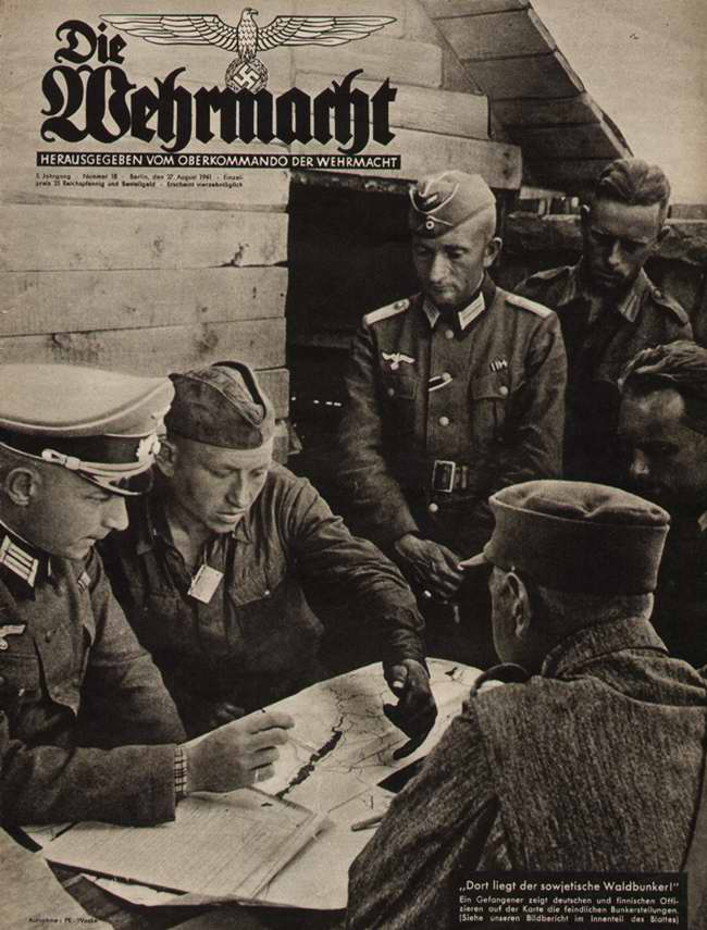 В этом лесу находятся советские подземные бункеры: пленный красноармеец указывает немецким и финским офицерам их местоположение на карте