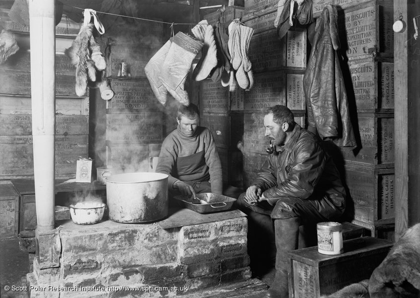 "Meares and Dimitri at the blubber stove in the ""Discovery"" Hut at Hut Point. November 3rd 1911-2"