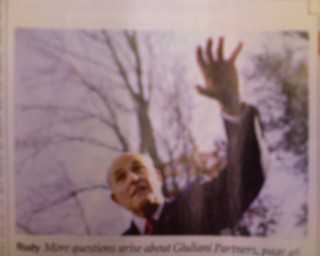 low-angled photo from Time Magazine showing Guliani raising a perspective-distorted arm as if to grasp at fleeing humans