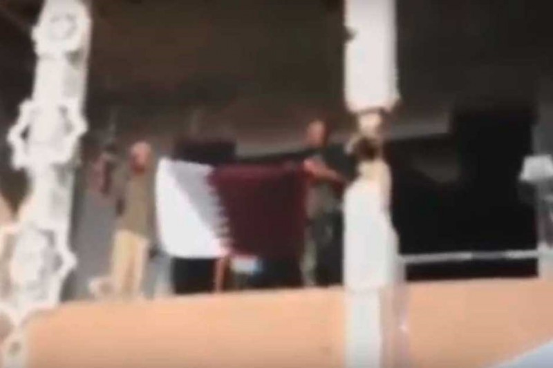 Катарские спецназовцы, разворачивающие катарский флаг у катарского посольства в Триполи