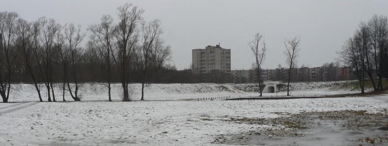 Так выглядит некогда грозная крепость. Видны восстановленные Западные ворота в земляном крепостном вале.  Вдалеке за крепостью — жилые дома постройки 1980-х годов.