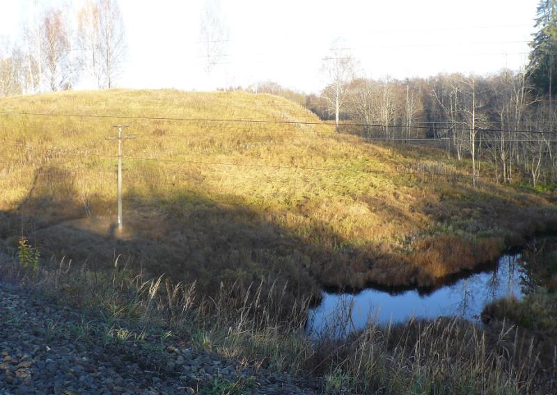 Земляной вал средневекового укрепления возведен на правом берегу реки так, что между ним и рекой остается предполье.