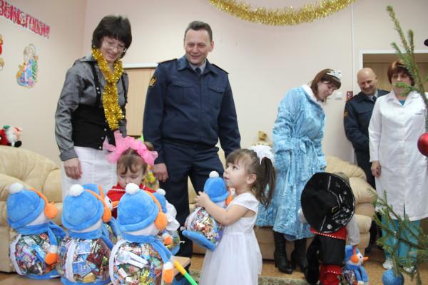 Начальник УФСИН Андрей Виноградов вручает детям подарки