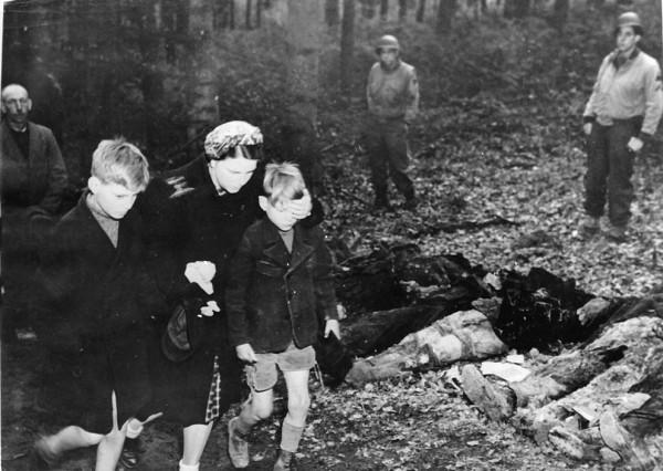 Немка закрывает рукой глаза своему сыну, проходя мимо 57 эксгумированных (сов гражда) тел возле Suttrop, Германия.