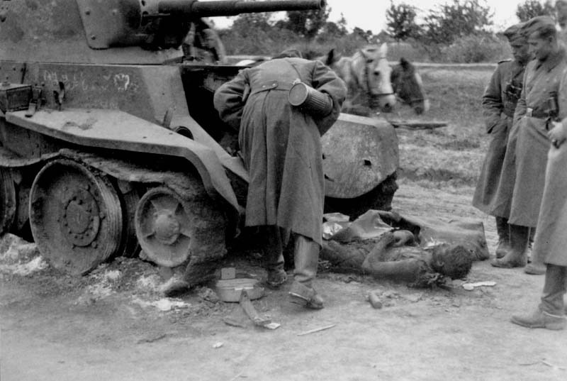 Wehrmacht soldiers inspecting dead crew member of the burned Soviet tank BT-7
