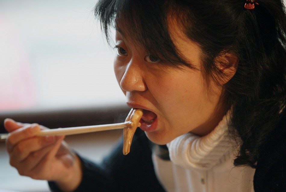 A Chinese woman eats from an ox and dog penis dish at the Guolizhuang
