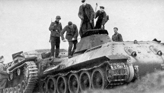 """Немцы вскрывают люк танка. Один с ломом, другой с топором. Самоходка """"""""Штуг III"""" слева."""