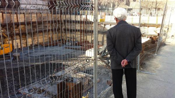 Пенсионер, наблюдающий за стройкой