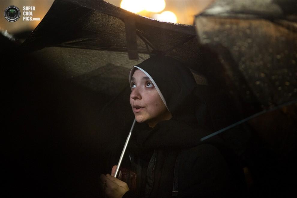 Монахиня под зонтом читает молитву