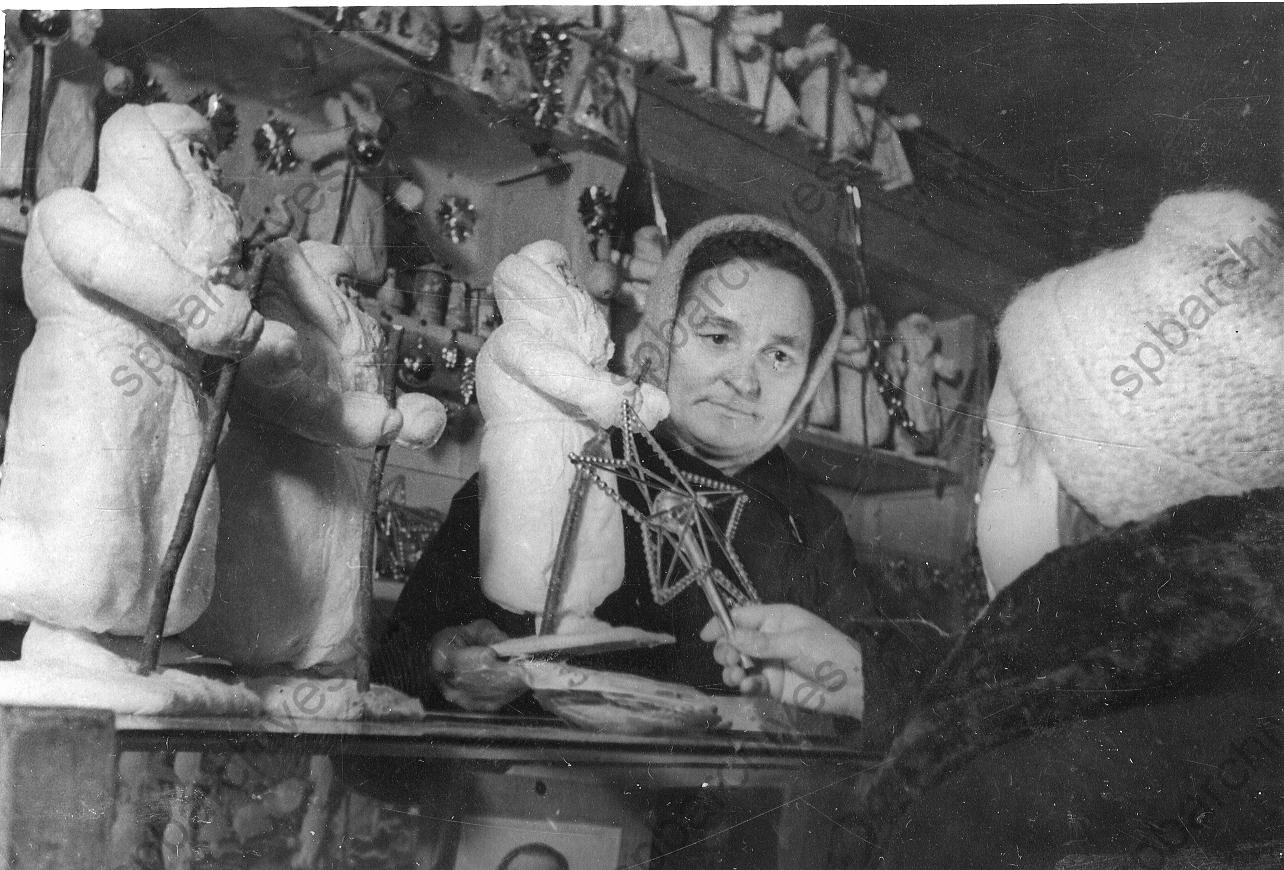 1942. Продавщица отдела игрушек одного из магазинов Ленпромторга К.И. Цыганенко показывает юной покупательнице елочные украшения