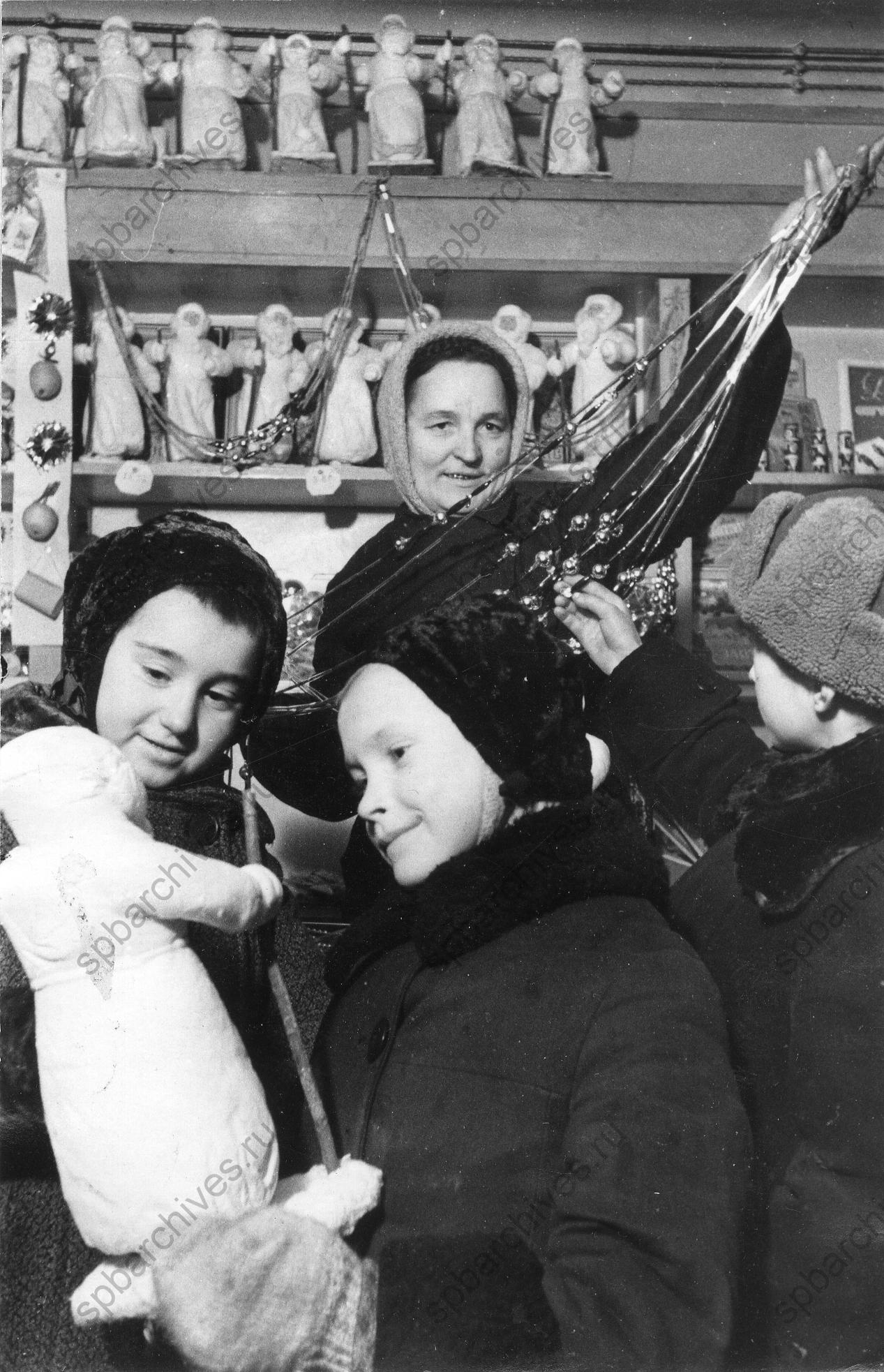1942. Юные покупатели в одном из магазинов Ленпромторга выбирают Деда Мороза