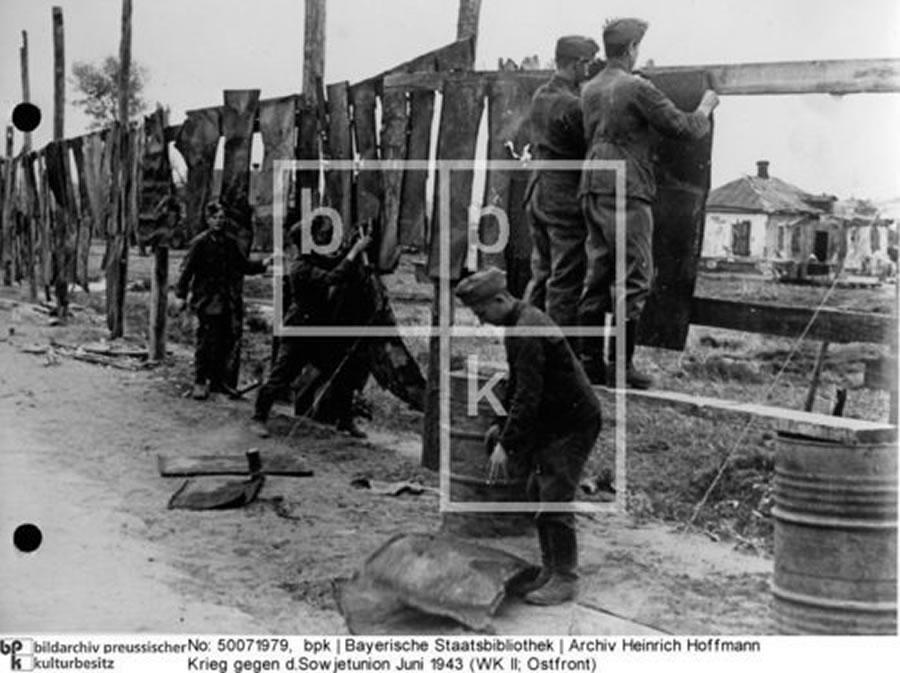 Juni 1943 (WK II; Ostfront). Soldaten beim Anbringen von Sichtschutz; neben e.Nachschubstraße. Kampf im Donez-Becken=Donets