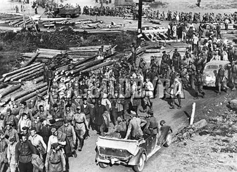 Hier passiert eine Kolonne sowjetischer Gefangener auf dem Wege in ein Sammellager eine im Bau befindliche Brücke.  Belgorod in Russland vom 17.7.1943