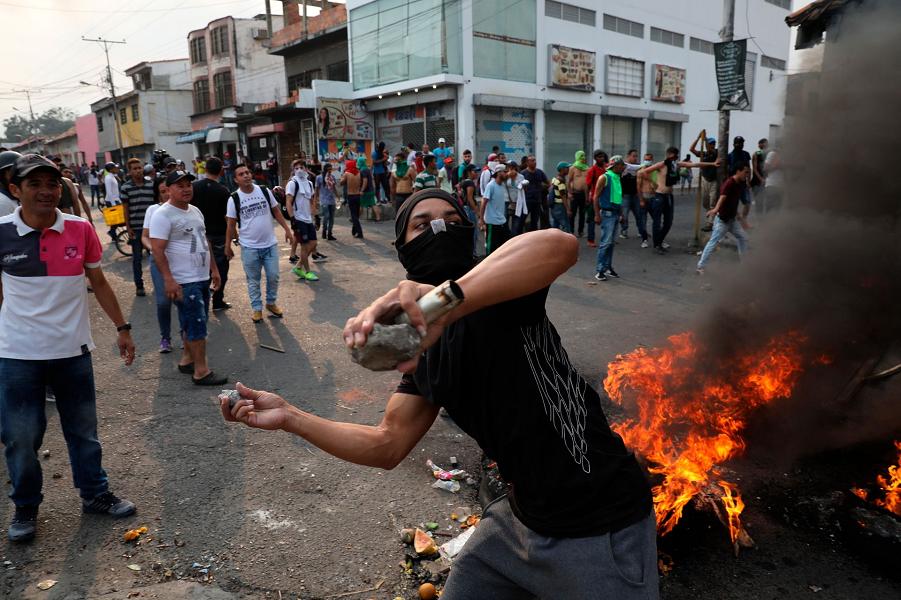 Демонстрант бросает камни во время столкновений с Боливарианской национальной гвардией в Урене, Венесуэла, недалеко от границы с Колумбией, в субботу…
