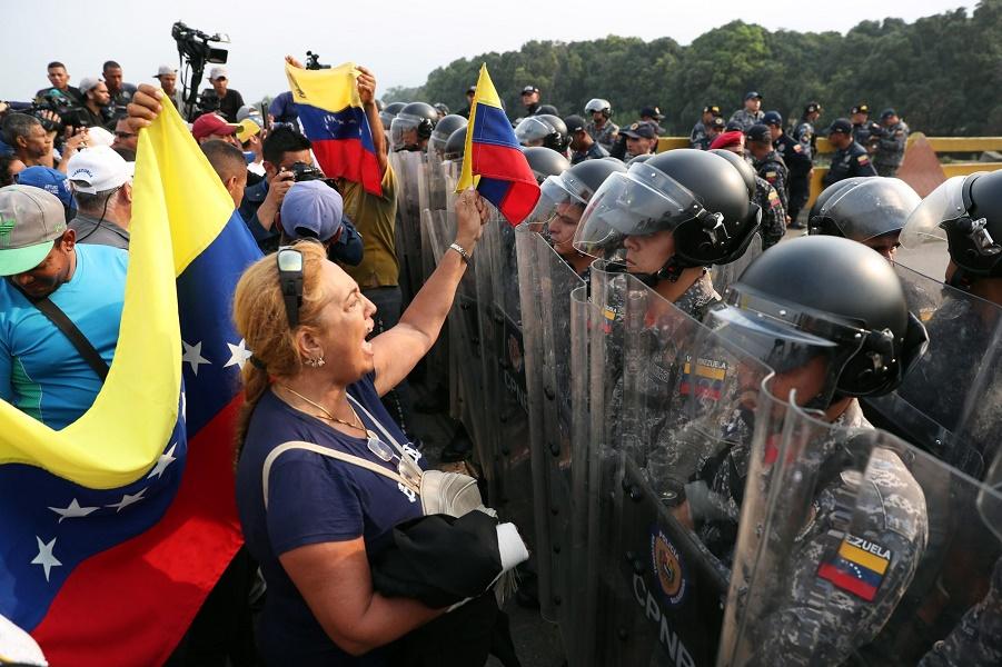 Венесуэльцы стоят перед военнослужащими вооруженных сил Венесуэлы у моста Симона Боливара на границе с Венесуэлой в Кукуте, Колумбия, 23 февраля 2019…