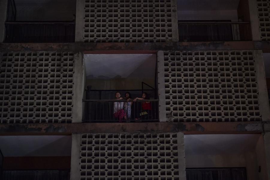 Женщины выходят из обесточенного многоквартирного дома в Каракасе 7 марта 2019 года.png