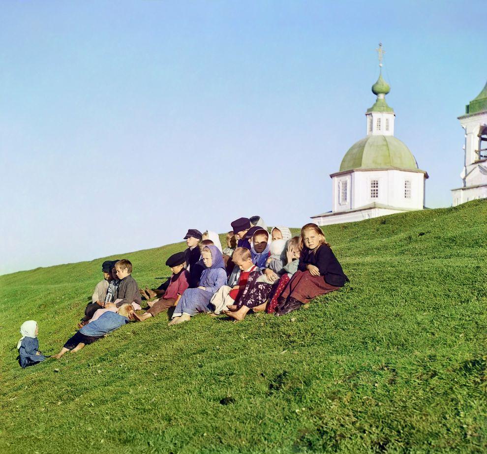 Русские дети сидят на холме недалеко от церкви у Белого озера, 1909