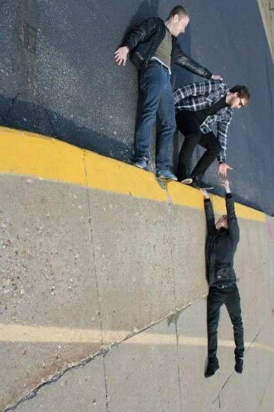Ребята удерживают товарища на отвесной стене