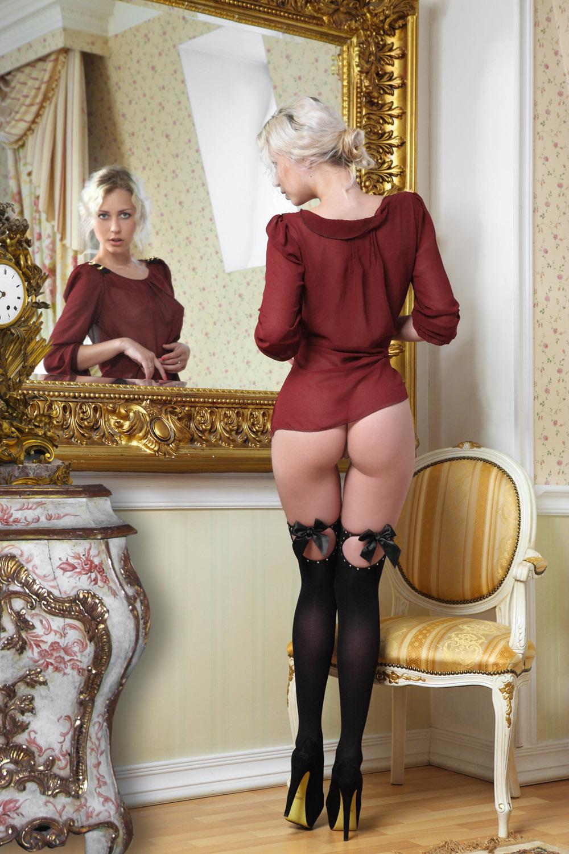 Одевает чулки перед зеркалом