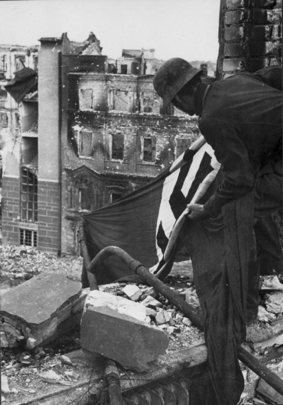 Немецкий солдат закрепляет фашистский флаг на здании в центре Сталинграда