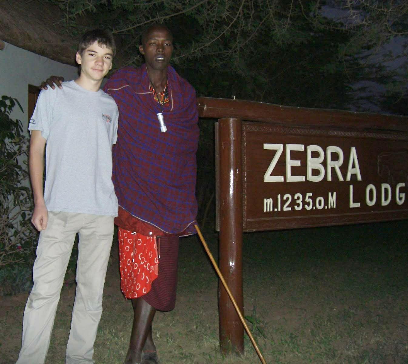 Это наш знакомый масай, который мне притащил копьё.На шее подаренный фонарик. Вот про дополнительные батарейки не подумали.