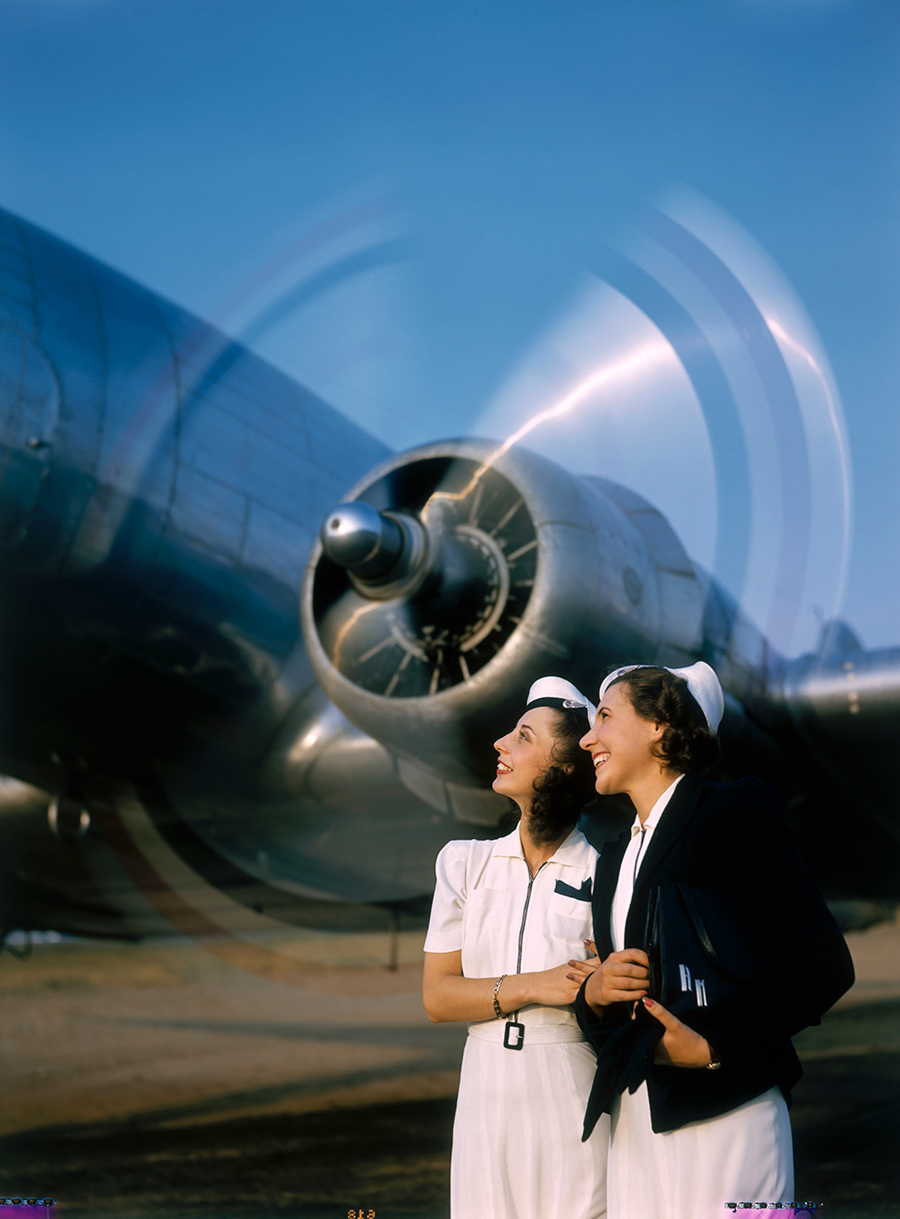 Two young women stand near a turning aircraft propeller  BY LUIS MARDEN, 1940.