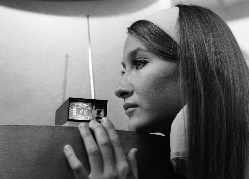 """A model looks at the Sinclair Microvision set, a pocket size television set designed by Clive Sinclair that can go anywhere and claims to be the world""""s smallest TV, at Earls Court, London, on September 1, 1966. 2"""""""""""