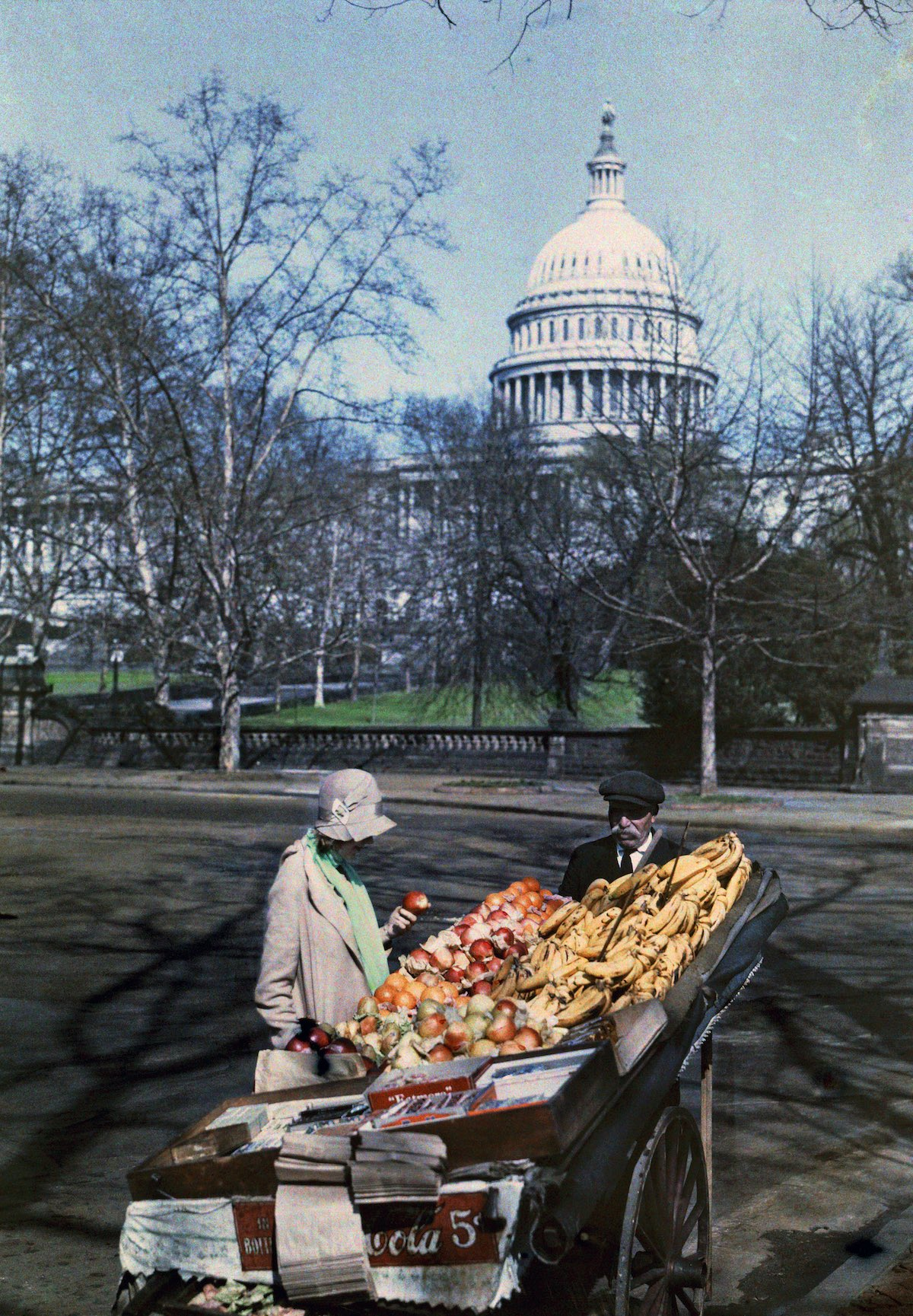 1930 Вашингтон, округ Колумбия – женщина перед стеллажом с фруктами в столице США. Orren Louden