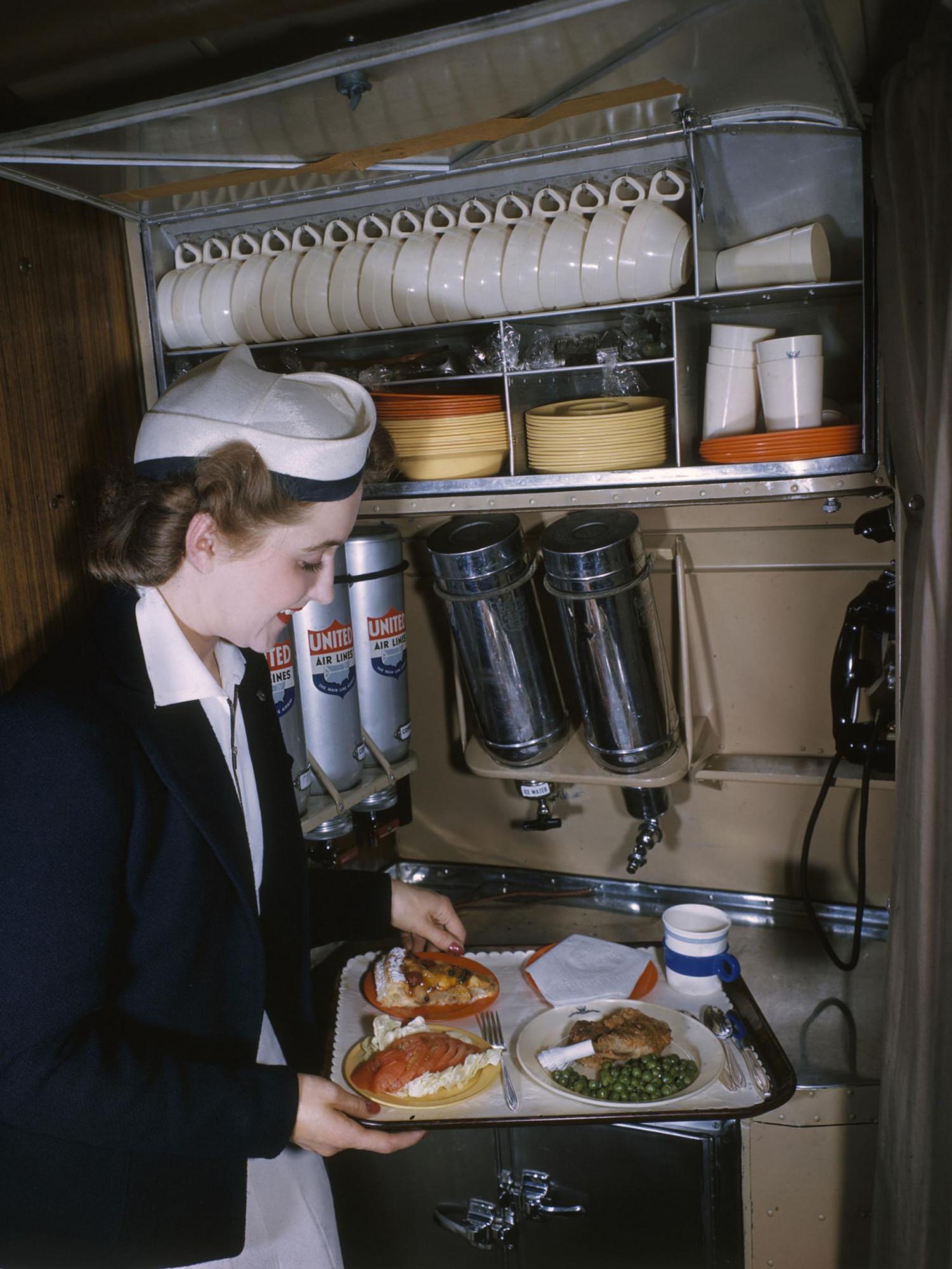 1940 Una azafata prepara una comida en un vuelo. Luis Marden