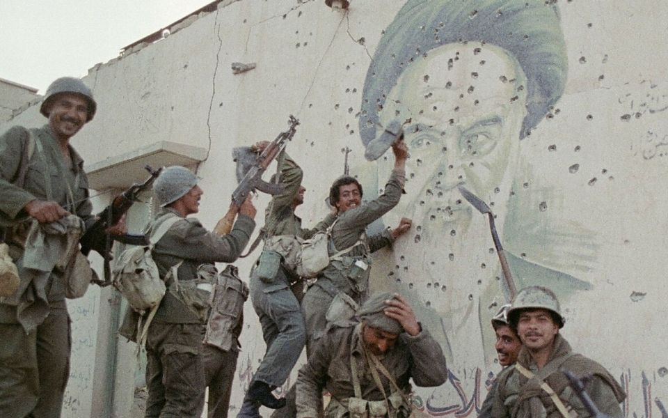 Iraqi soldiers pose in front of a bullet-riddled mural of Iranian leader Ayatollah Khomeini, April 20, 1988. Mike Nelson