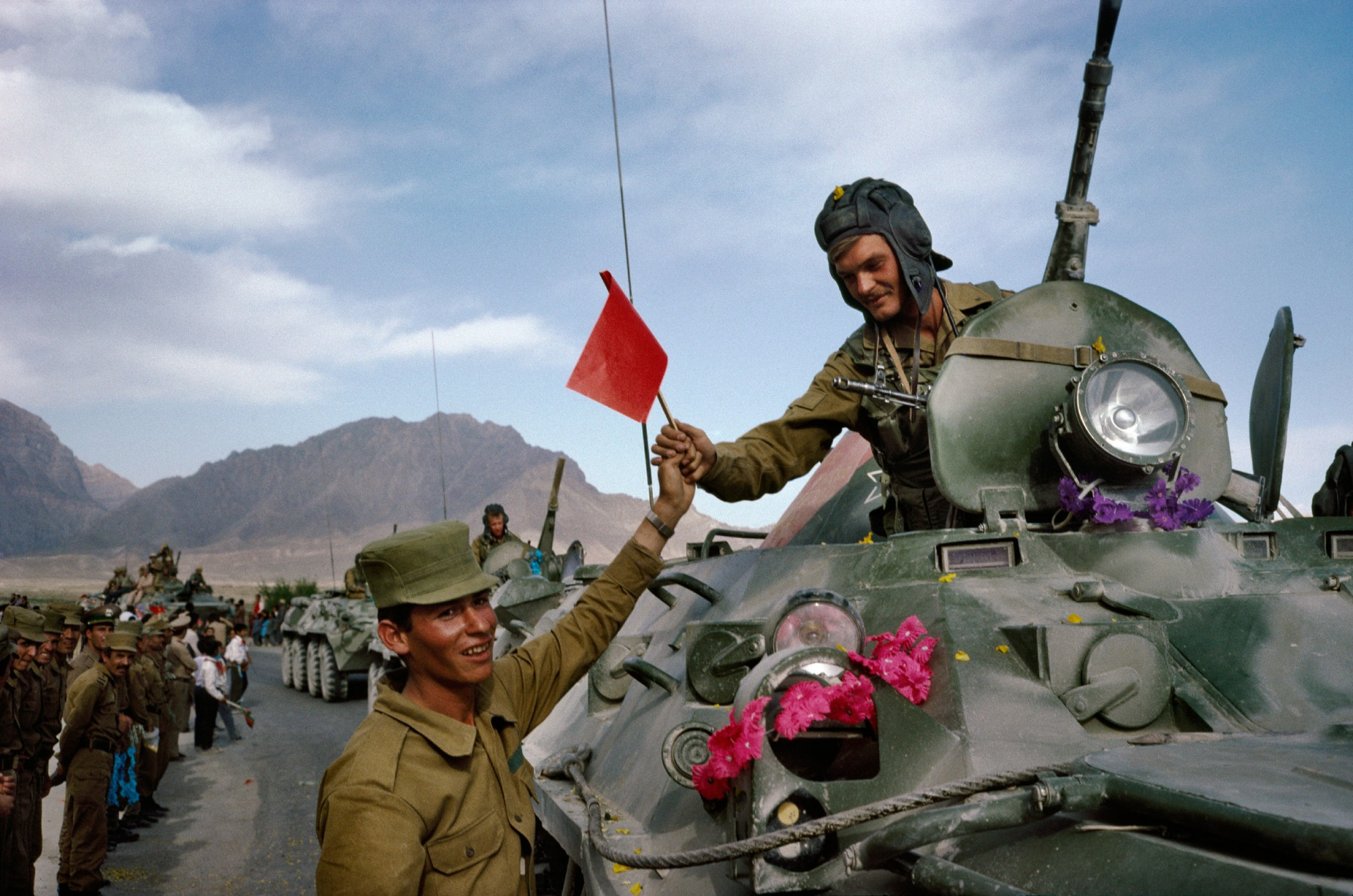 On the first day of the Soviet withdrawal from Afghanistan in May 1988, an Afghan soldier hands a flag to a departing Soviet soldier in Kabul