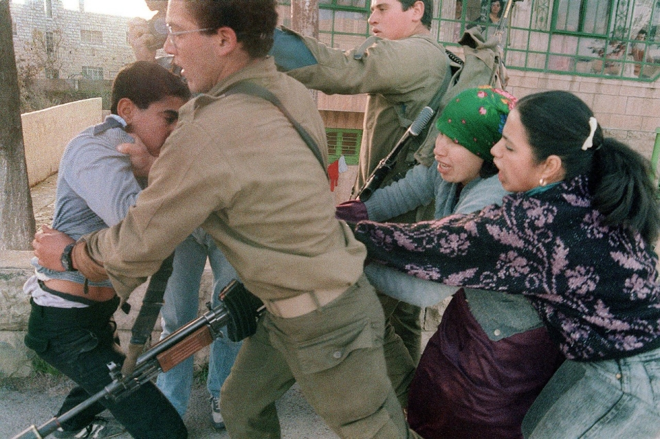Ramallah, 1988. A Palestinian mother and elder sister try to stop an Israeli soldier from taking away a Palestinian boy arrested for rock throwing.Esaias Baitel