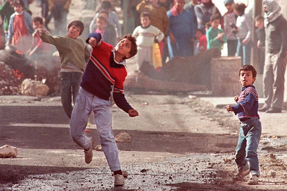 Ramallah, 1988. Children throw stones at Israeli soldiers in the Amari refugee camp. Eric Feferberg