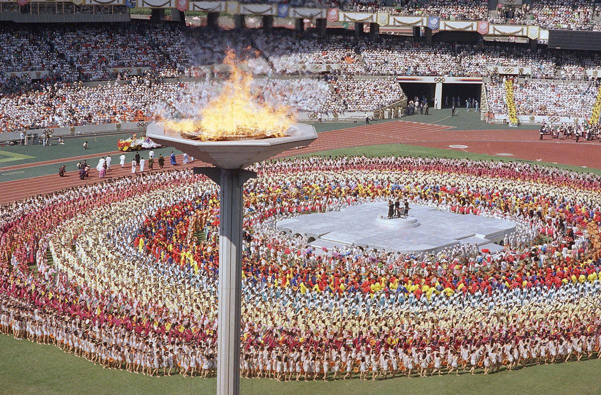 Олимпийский факел горит над Олимпийским стадионом, 17 сентября 1988 года, во время церемонии открытия летних Олимпийских игр в Сеуле