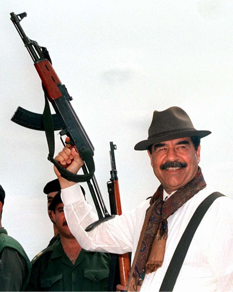 1998 Saddam Hussein brandishes a Russian-made AK-47 assault rifle during his visit to villages in northern Iraq