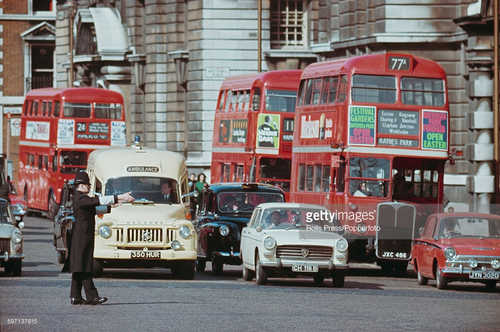 1968 Лондон AEC Regent III RT and Routemaster London buses and an ambulance along Whitehall