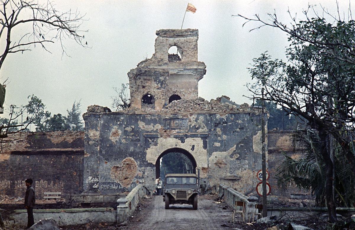 1968 Флаг Республики Вьетнам развевается на главной башне старой крепости, на фоне которой джип пересекает мост через реку Хюэ, во время Тетского наступления