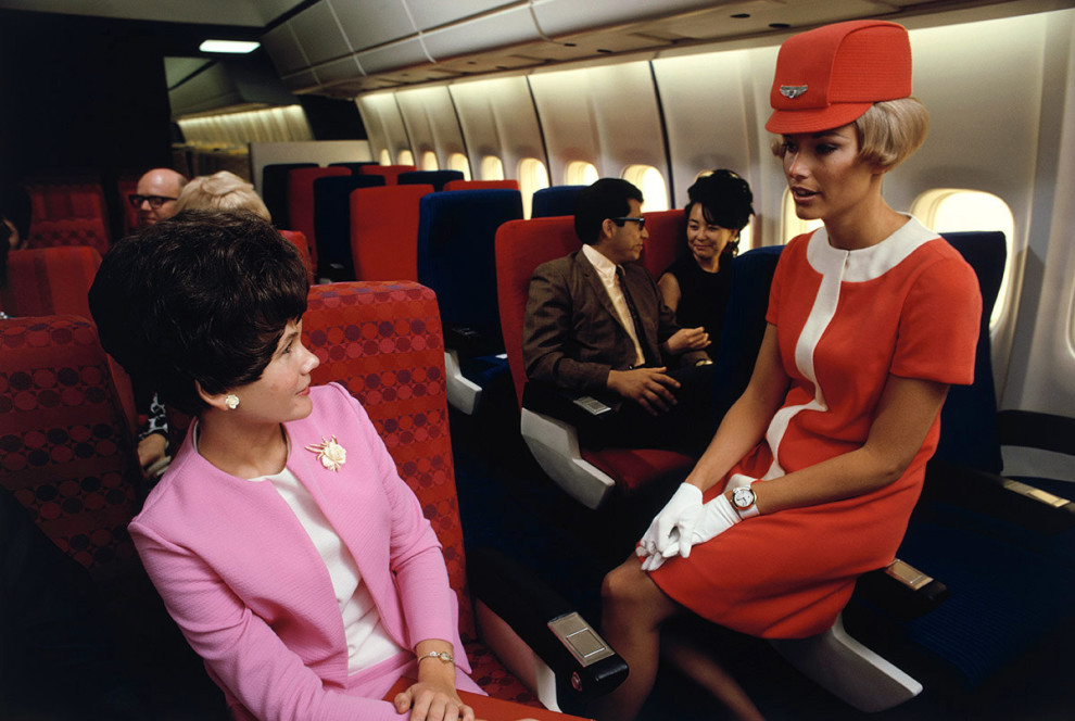 1968 A United Airlines flight attendant talks with a passenger aboard a Douglas DC-10. Dean Conger