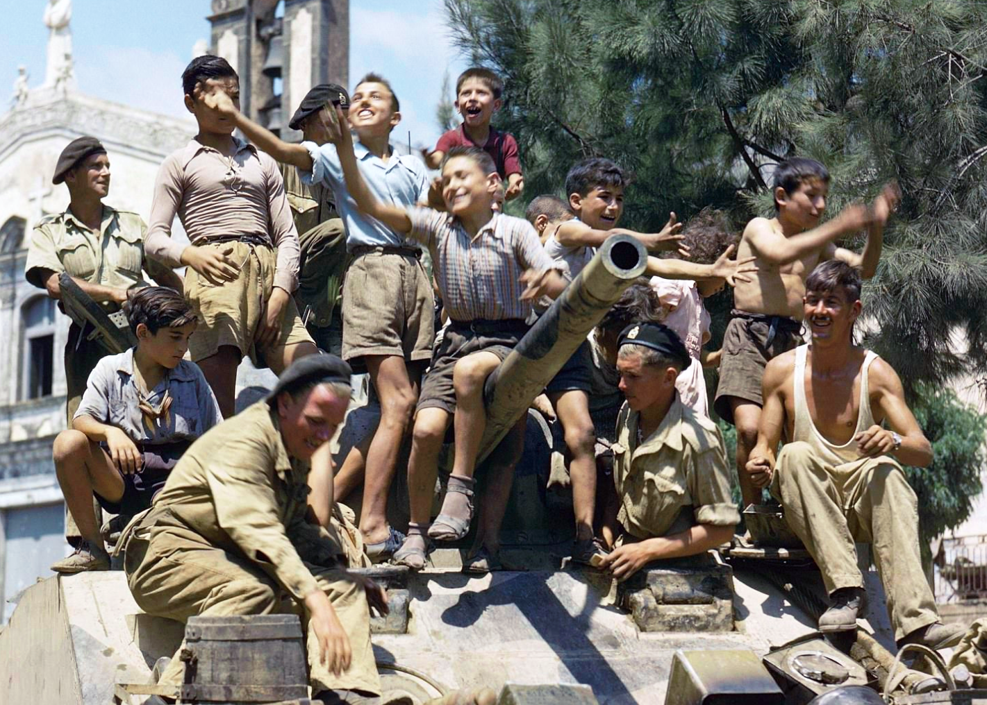 August 1943 Local children crowding aboard a Sherman tank of the 3rd County of London Yeomanry in Sicily