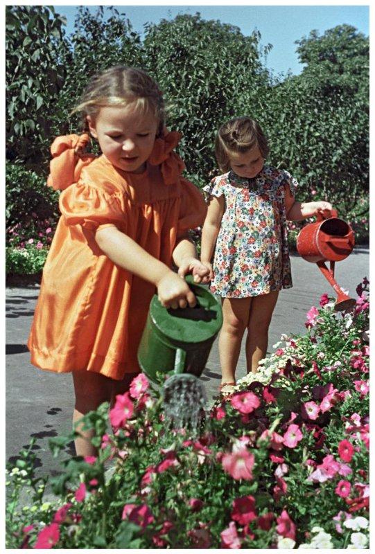 1953  «Нам хорошо живется». Детский сад № 1 завода «Арсенал» Печерского района Киева. Заботливо ухаживают за цветами, посаженными на территории садика. Н.Козловский
