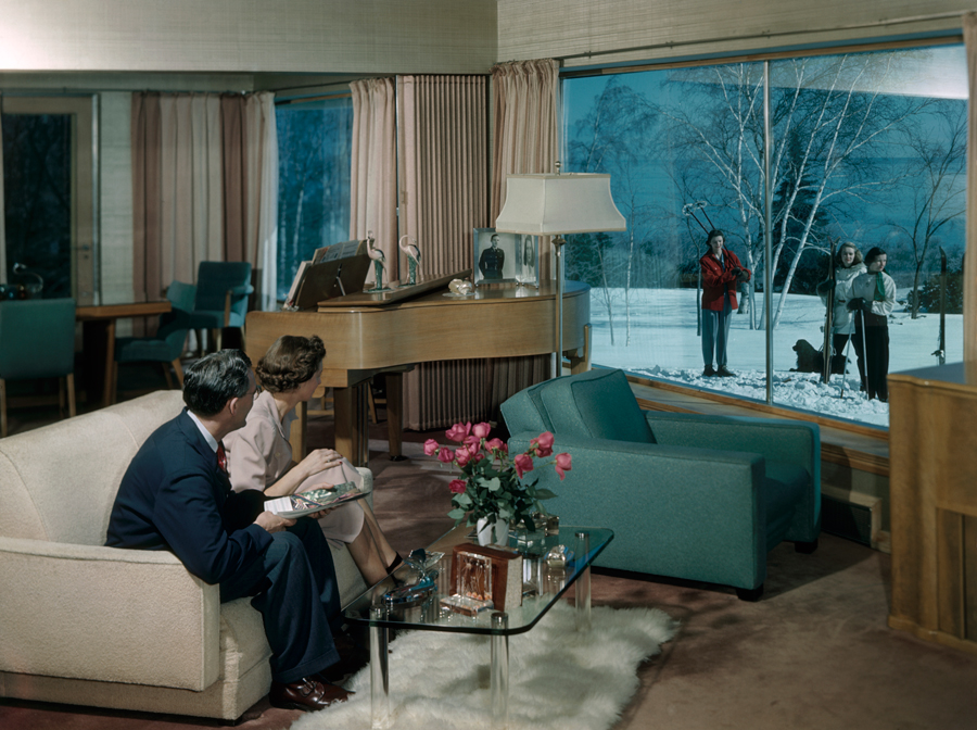 1949 A couple seated in a living room looks out a window at skiers on lawn in Duluth Minnesota