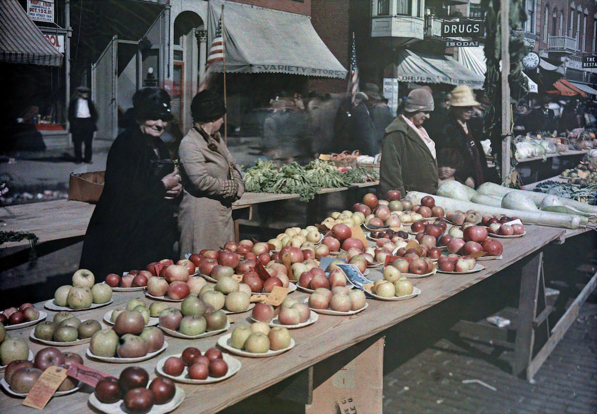 1929 Ohio - Four women stand beside an apple stand at a fair in Loundonville