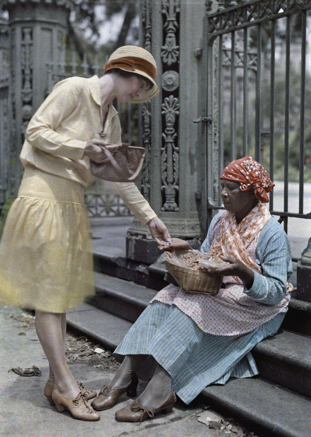 1929c New Orleans, Louisiana - A woman sitting on stone steps in The French Quarter sells pralines Wisherd