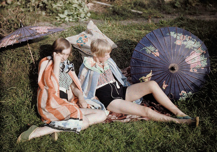 Two young girls enjoy the sun relaxing in their suits and wraps in England by Bernard Wakeman 1929