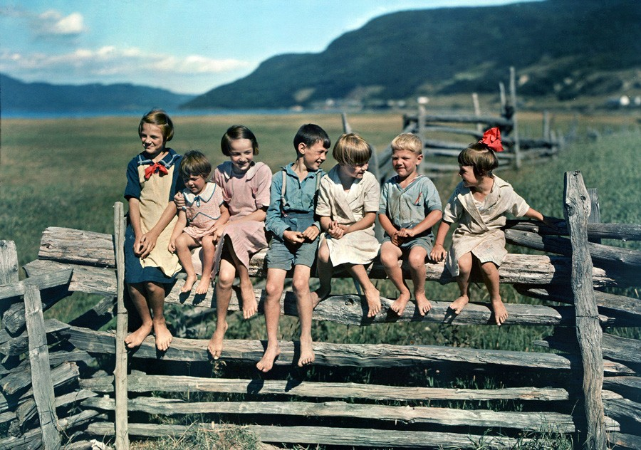 1939 may Seven siblings sit on a wooden fence in Quebec by Howell Walker