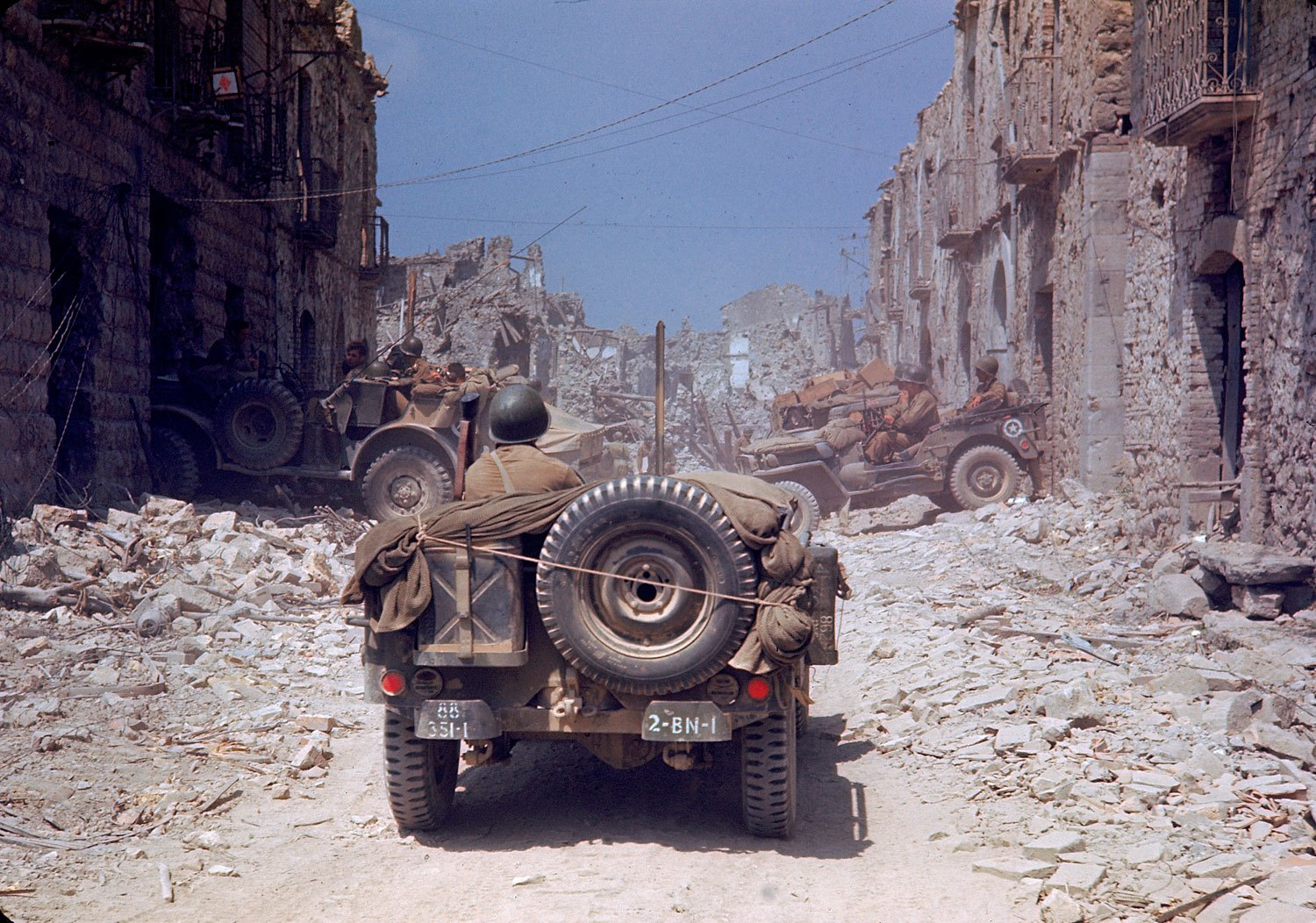 1944 American jeeps travel through a bombed-out town during the drive towards Rome