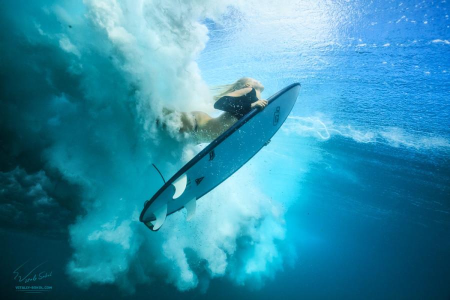 Surfing Girl doing DuckDive under beautiful ocean WAVE