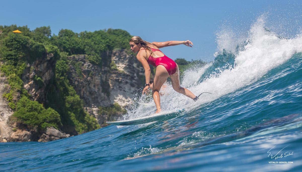 Surfer Girl Riding a big blue ocean wave